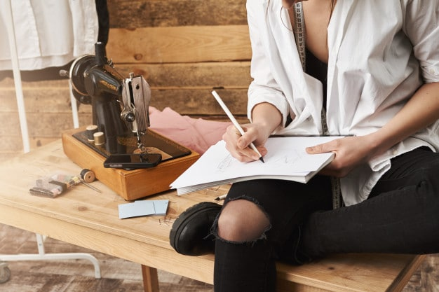 when-hobby-become-real-work-cropped-shot-creative-female-designer-clothes-sitting-table-near-sewing-machine-her-workshop-making-notes-planning-new-design-her-clothing-line_176420-14572-1 (1)